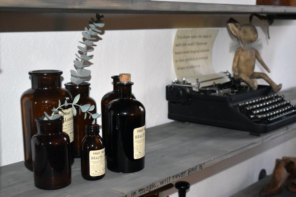 wohnzimmer deko Industrialstyle alte Flaschen alte schreibmaschine